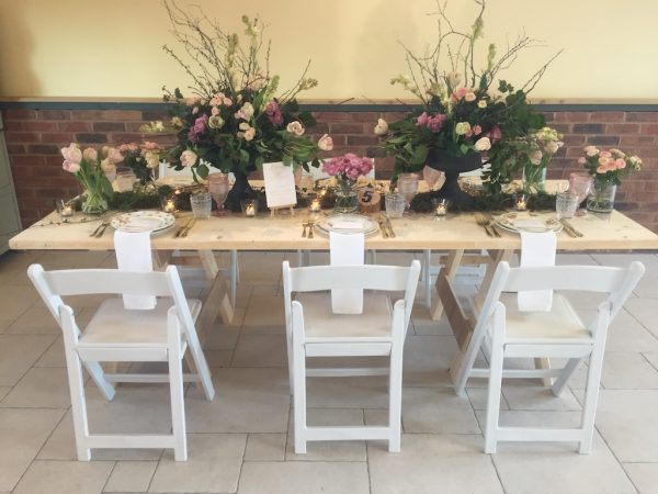 white folding chairs with plank table
